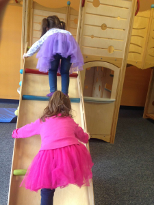 two girls playing on a structure