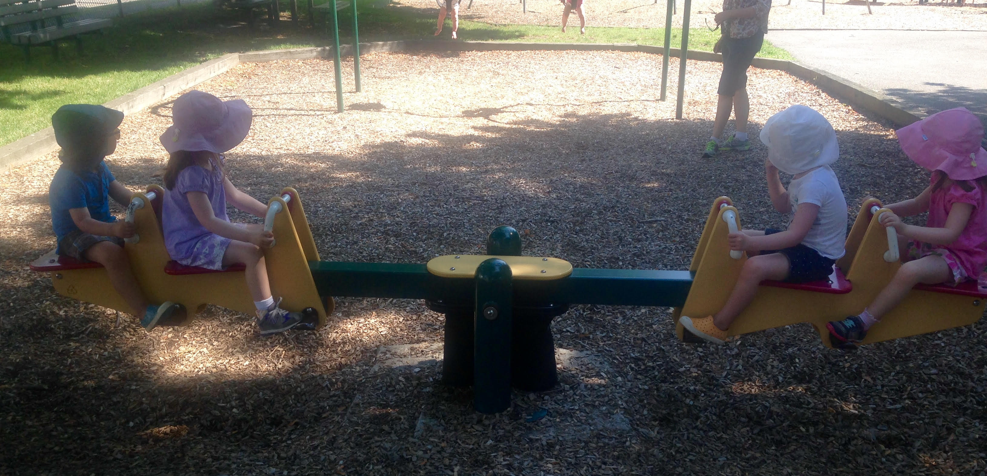 two sets of twins on a seesaw in a park